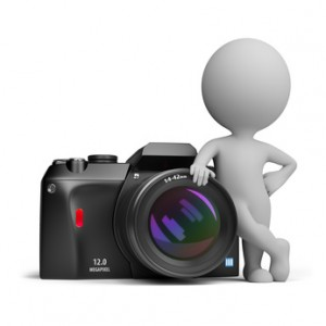 3d small person standing next to a large digital camera. 3d image. Isolated white background.